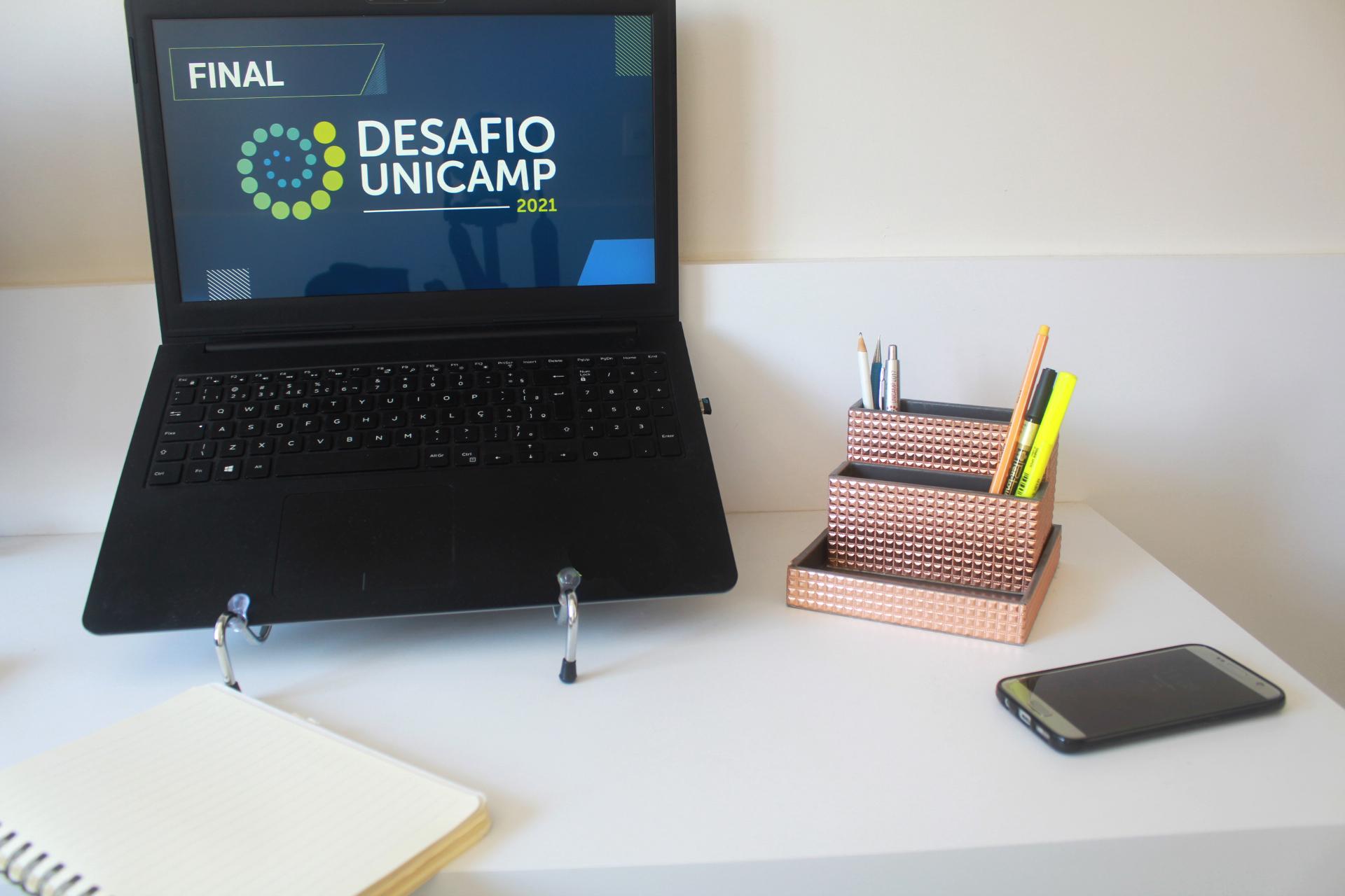 Mesa com tela de computador escrito Final Desafio Unicamp, caderno, porta lápis e celular.