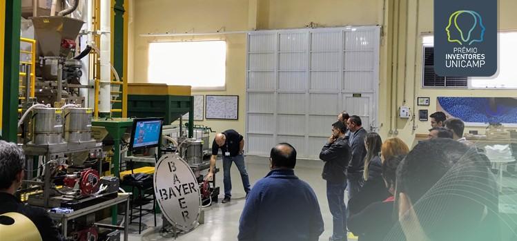 Máquina de processamento de sementes da Bayer exposta com várias pessoas ao redor
