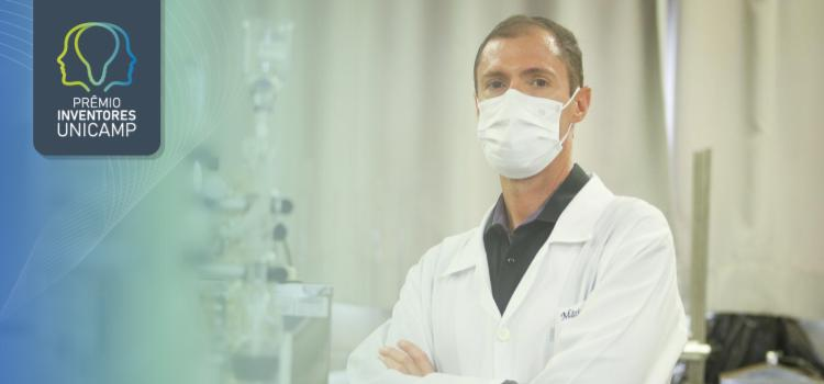 Professor Mário Maróstica vestindo um jaleco branco com máscara branca e de braços cruzados. Ele possui cabelo raspado e pele branca.