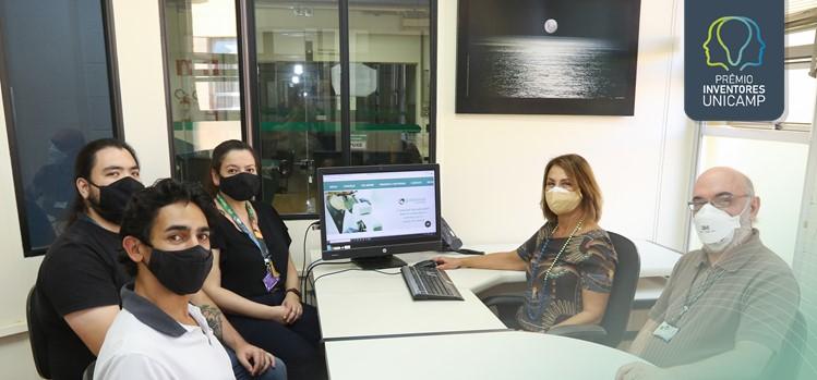Ao redor de uma mesa com o computador ligado mostrando a plataforma estão sentados e usando máscaras: Prof. José Gontijo, Cleusa Milani, Fabiana de Souza, Gabriel Ishizaki e Newton da Silva (FCM Unicamp)