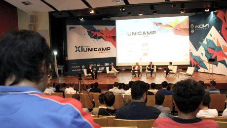 Auditório com pessoas assistindo debate de 5 pessoas sentadas em cadeiras no palco. Ao fundo, painel da Unicamp Ventures