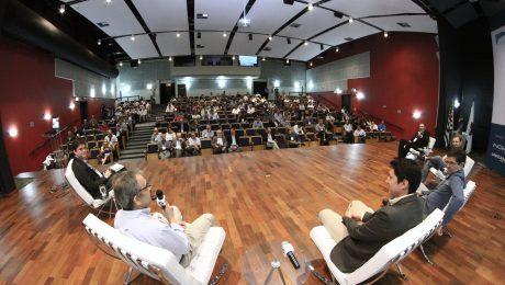 Cinco pessoas sentadas debatendo no palco de um auditório com plateia