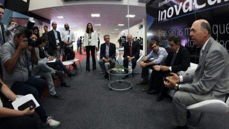 Executivos sentados em círculo e debatendo com painel de InovaCampinas ao fundo