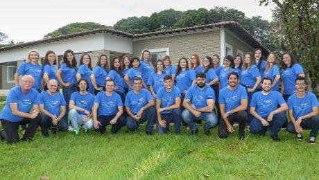 Equipe da Inova Unicamp reunida em frente à sede na fazenda argentina, todos com a camiseta azul de comemoração dos 15 anos da Agência