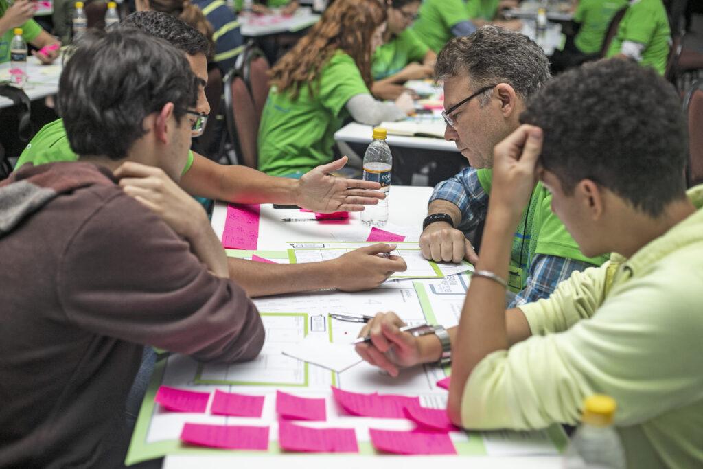 Mesa com Lean Canvas preenchido com post-its, três membros de equipe mais um mentor empresarial