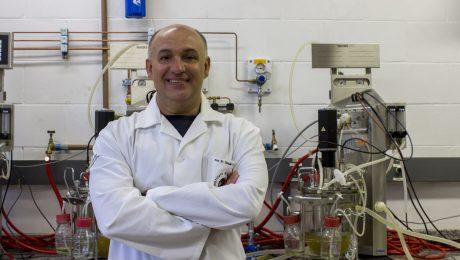 Prof. Gonçalo de jaleco, sorrindo em frente à equipamentos do laboratório