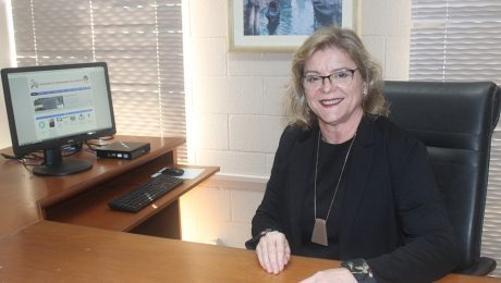 Prof. Mirna Gigante, diretora da FEA, está sentada sorrindo em seu escritório