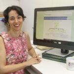Prof. Vera Lúcia sentada em frente ao programa de computador