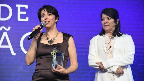 Prof. Vera Lucia discursando no microfone com troféu