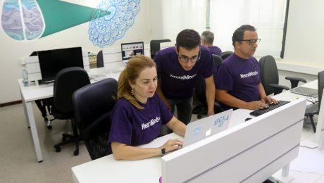 Laboratório da NeuralMind com computadores e 4 funcionários trabalhando