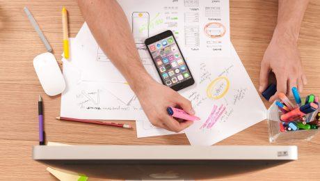 Mãos e braços de um homem branco em frente de um computador com papéis, celular e várias canetas montando um cronograma e aparentando estar organizando algo