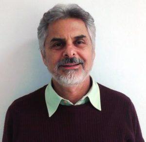 Homem aparentando carca de 60 anos. Veste uma blusa de frio marrom e uma camisa verde claro, da qual só aparece a gola. O homem tem cabelos, barba e bigode grisalhos, sobrancelhas escuras e está sorrindo. O fundo da foto é uma parede branca.