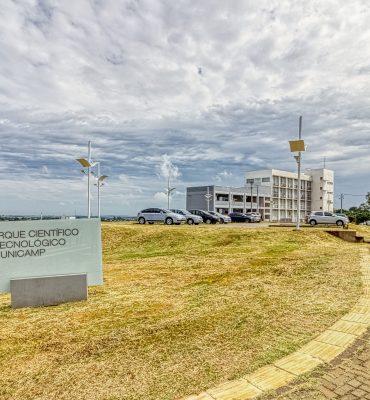 A foto mostra a placa do Parque Científico e Tecnológico da Unicamp e, ao fundo, prédios que fazem parte do Parque.