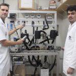 Dois homens, pesquisadores da Unicamp, vestindo jaleco branco, aparecem em frente ao equipamento usado na produção de aromas naturais de frutas. A máquina tem estrutura metálica, da altura dos cientistas, além de tubos pretos e mostradores digitais.