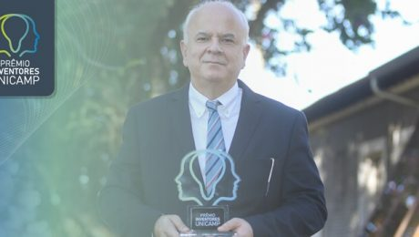 Diretor da faculdade segura troféu. Ele é um homem de cerca de 50 anos, branco, com cabelos também brancos. Veste terno e está na área externa da Inova