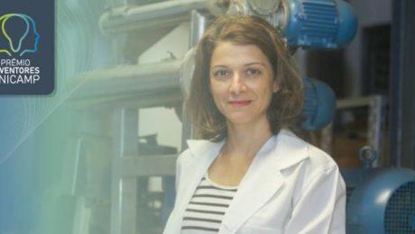 Na foto está a professora Ana Silvia Prata, vestindo um jaleco branco por cima de uma camiseta listrada preto e branca. A professora possui cabelo na cor castanho na altura do ombro.
