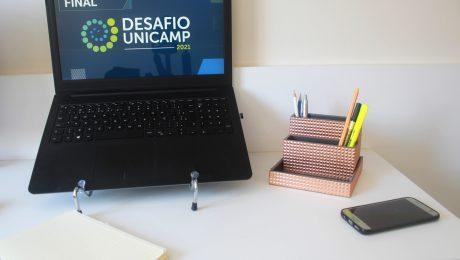 Mesa com computador escrito Final Desafio Unicamp, caderno, porta-lápis e celular
