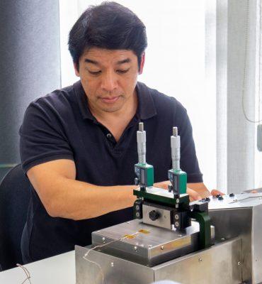 Homem de camisa escura sentado em uma cadeira atrás de uma mesa olhando para um equipamento