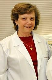 Professora Carmen tem cabelos curtos, veste blusa vermelha e jaleco branco