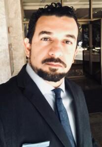 Homem de cabelos encaracolados, com barba e bigode, veste terno com gravata