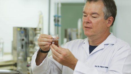 Pesquisador de jaleco branco segura um recipiente de forma cilíndrica contendo mel descristalizado