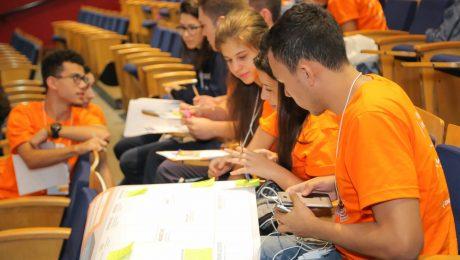 Jovens em auditório conversando com cartazes e papéis. Eles estão com camiseta laranja.