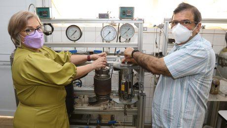 Os pesquisadores estão mexendo no aparelho de extração supercrítica dentro do laboratório, ambos estão de máscara.