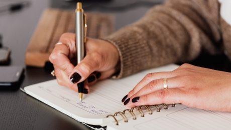 A imagem foca na mão de uma mulher escrevendo um uma agenda.