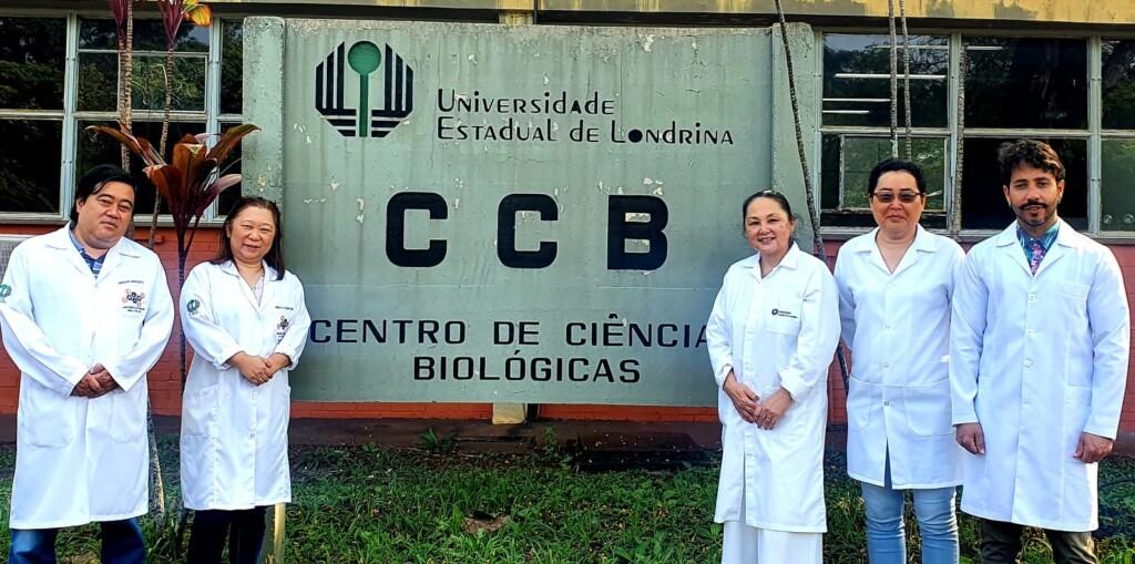 grupos de cinco pesquisadores com jalecos brancos que posam para foto em frente a placa da UEL