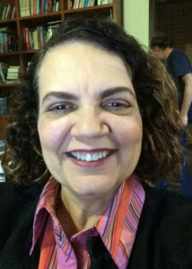 A professora Maria Teresa tem cabelos cacheados e sorri para a foto