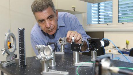 Homem, cabelos grisalhos, veste camisa azul e mexe em equipamentos de pesquisa