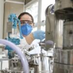 Pesquisadora mulher com máscara e luvas azuis mexe em equipamentos em laboratório de pesquisas